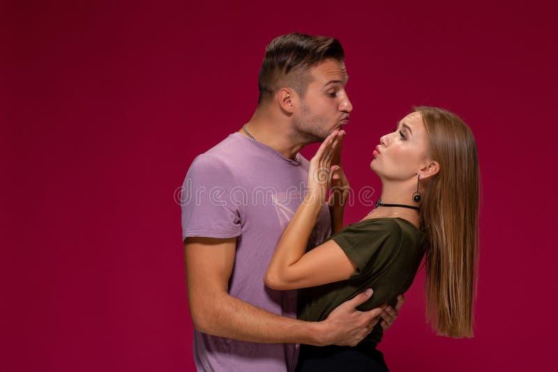 Portrait de la femme contrariée outragée faisant des gestes pour s'arrêter avec la main tandis qu'homme essayant de l'embrasser s images libres de droits