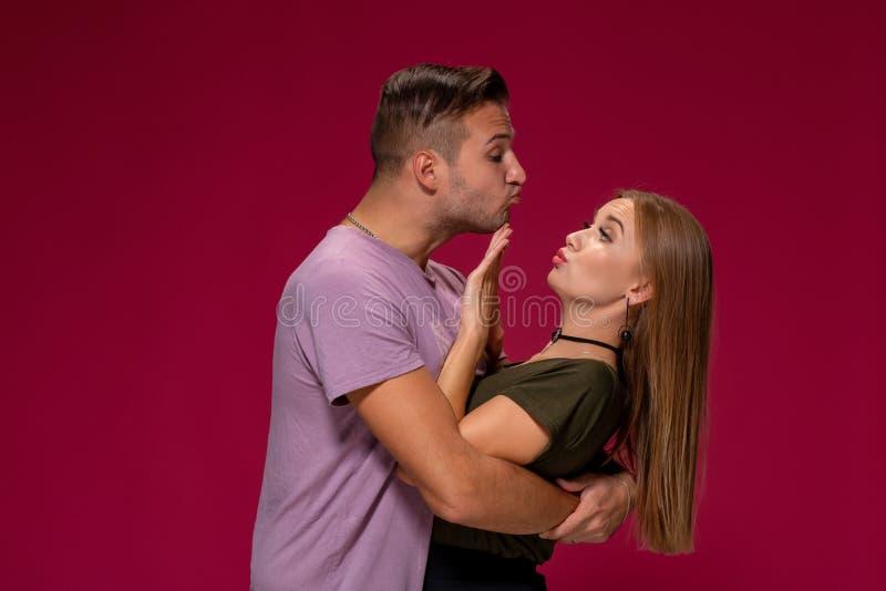 Portrait de la femme contrariée outragée faisant des gestes pour s'arrêter avec la main tandis qu'homme essayant de l'embrasser s images stock