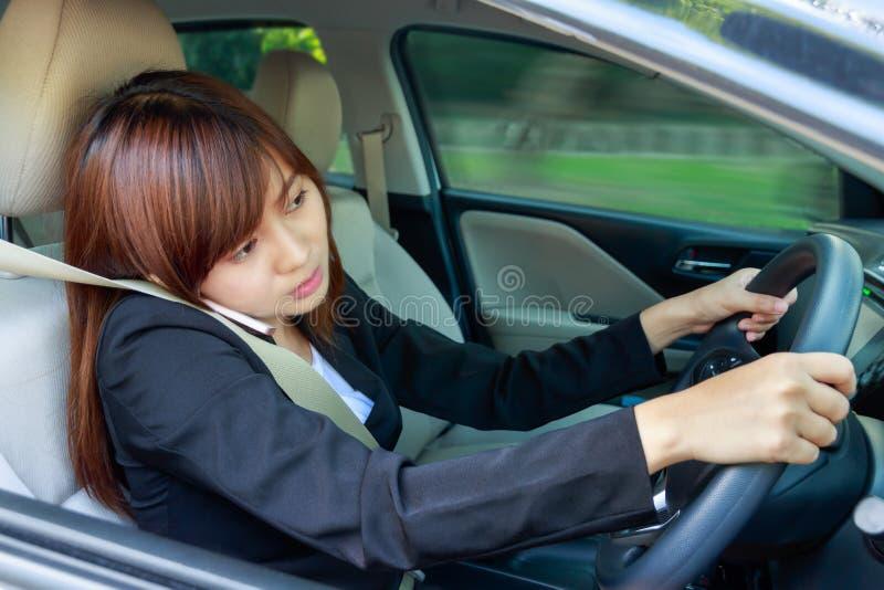 Portrait de la femme d'affaires à l'aide du téléphone intelligent tout en conduisant la voiture images stock