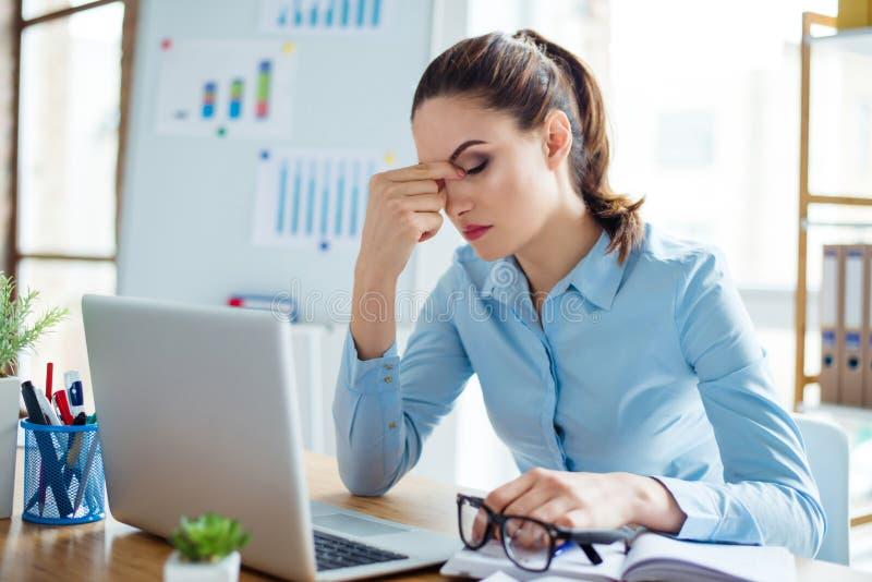 Portrait de la femme d'affaires fatiguée ayant le mal de tête sur le lieu de travail à l'arrière photos stock