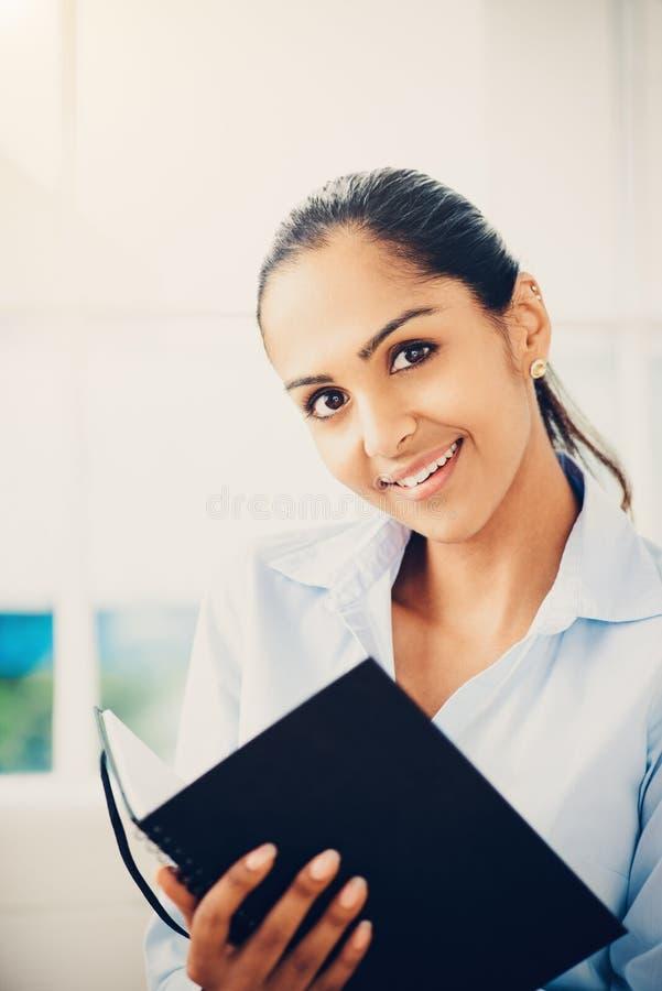 Portrait de la femme d'affaires indienne attirante travaillant de la maison photos stock