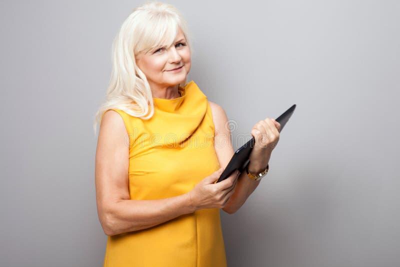 Portrait de la femme d'affaires supérieure attirante à l'aide du comprimé photos stock