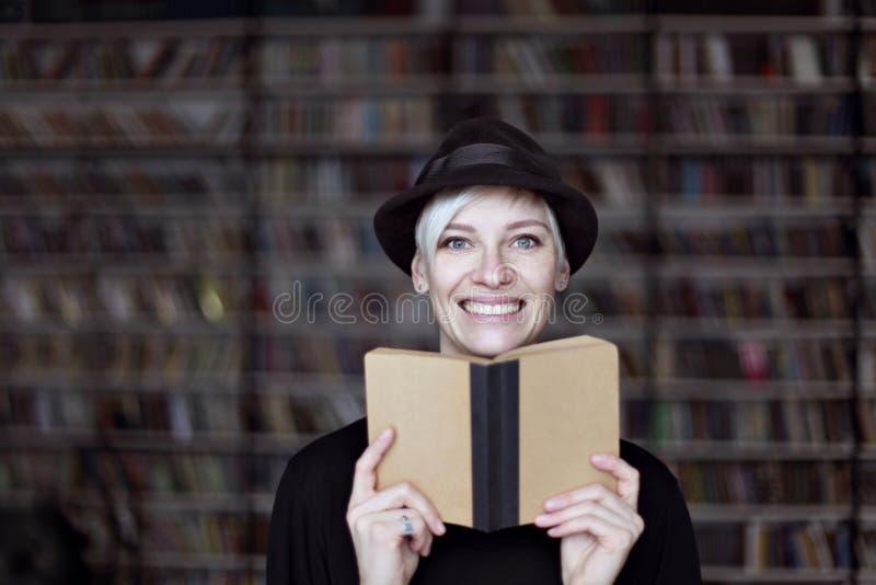 Portrait de la femme dans le chapeau noir avec le livre ouvert souriant dans une bibliothèque, cheveux blonds Fille d'étudiant de images libres de droits