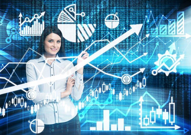Portrait de la femme de sourire qui précise les diagrammes financiers numériques bleus photo libre de droits