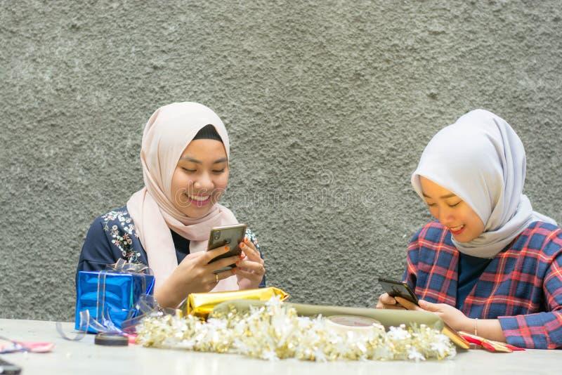 Portrait de la femme de deux hijab ? l'aide du bo?te-cadeau de whith de smartphone photos stock
