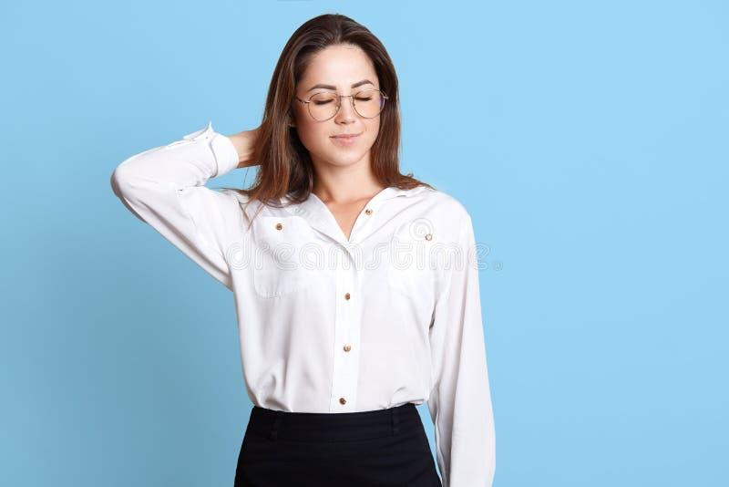 Portrait de la femme fatiguée d'affaires avec douleur cervicale, jeune femme caucasienne dans le tenue de soirée massant son cou  photo stock
