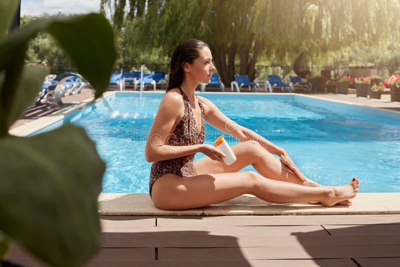 Portrait de la femme focalisée attentive posant près de la piscine au-dessus du fond de salon de cabriolet, étant humide après la images libres de droits