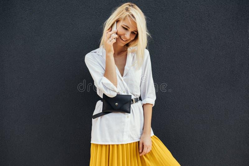 Portrait de la femme heureuse blonde d'affaires souriant et se tenant contre le mur du bâtiment gris tout en parlant sur le télép photographie stock