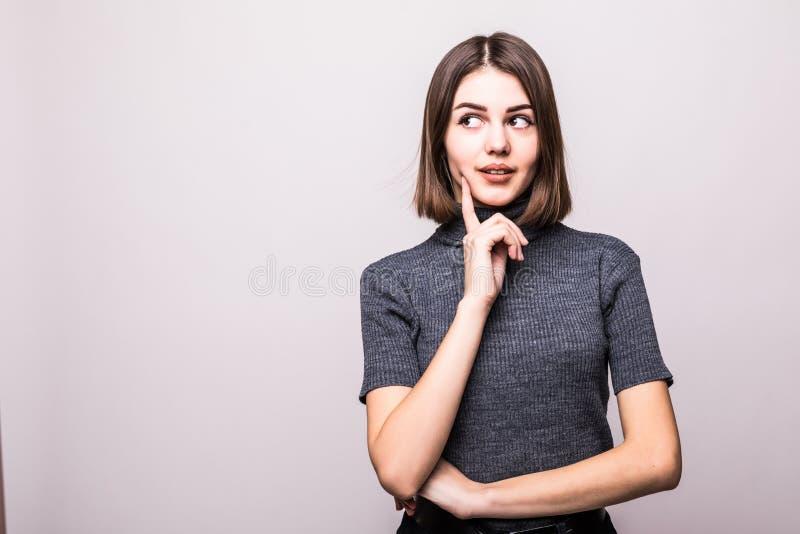 Portrait de la femme heureuse occupée attirante rêvant du smth sur le gris image stock