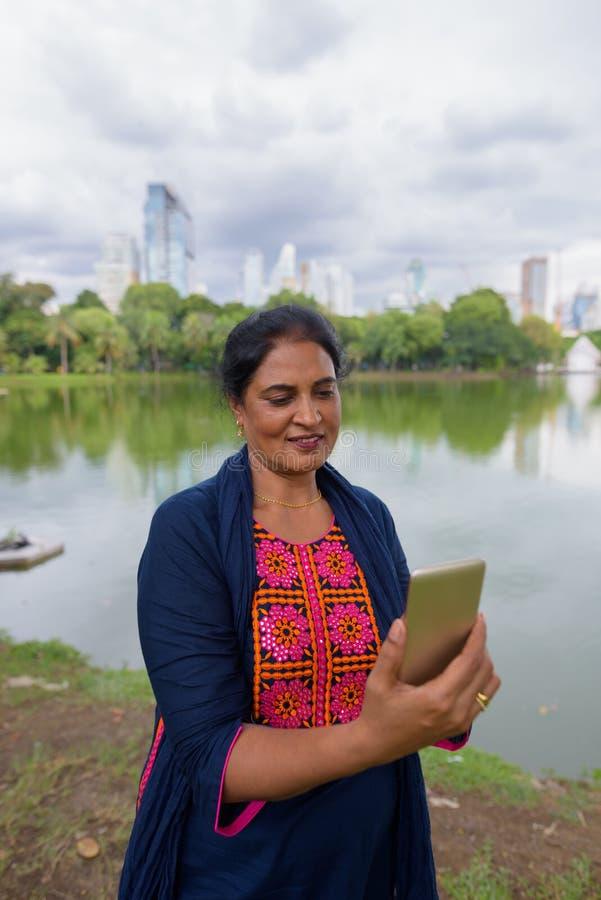 Portrait de la femme indienne mûre à l'aide du téléphone portable au parc photographie stock libre de droits
