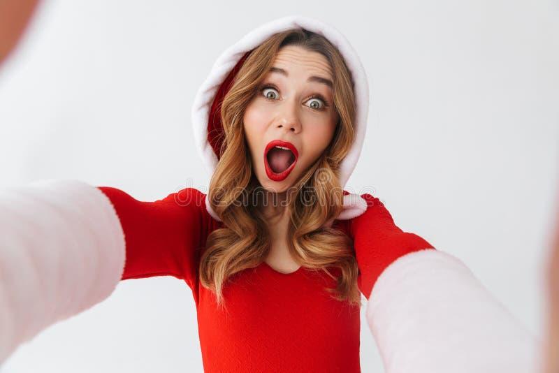 Portrait de la femme joyeuse 20s utilisant le costume rouge de Santa Claus souriant et prenant la photo de selfie, d'isolement au photos libres de droits