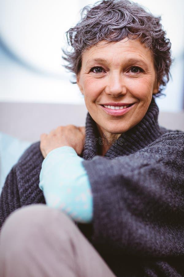 Portrait de la femme mûre heureuse s'asseyant sur le sofa photo libre de droits