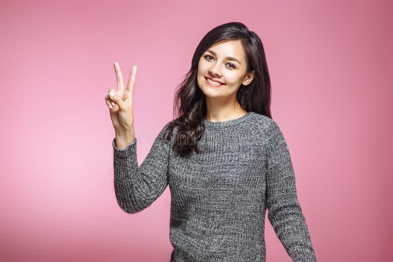 Portrait de la femme magnifique de brune regardant l'appareil-photo avec le sourire et montrant le signe de paix avec des doigts  photos stock