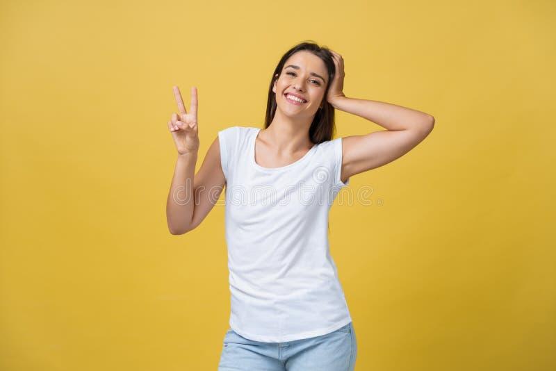 Portrait de la femme magnifique de brune regardant l'appareil-photo avec le sourire et montrant le signe de paix avec des doigts  photo libre de droits