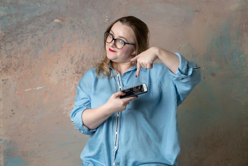 Portrait de la femme plus attirante de taille faisant se demander des ?motions avec le t?l?phone ? disposition au-dessus du fond  photos stock