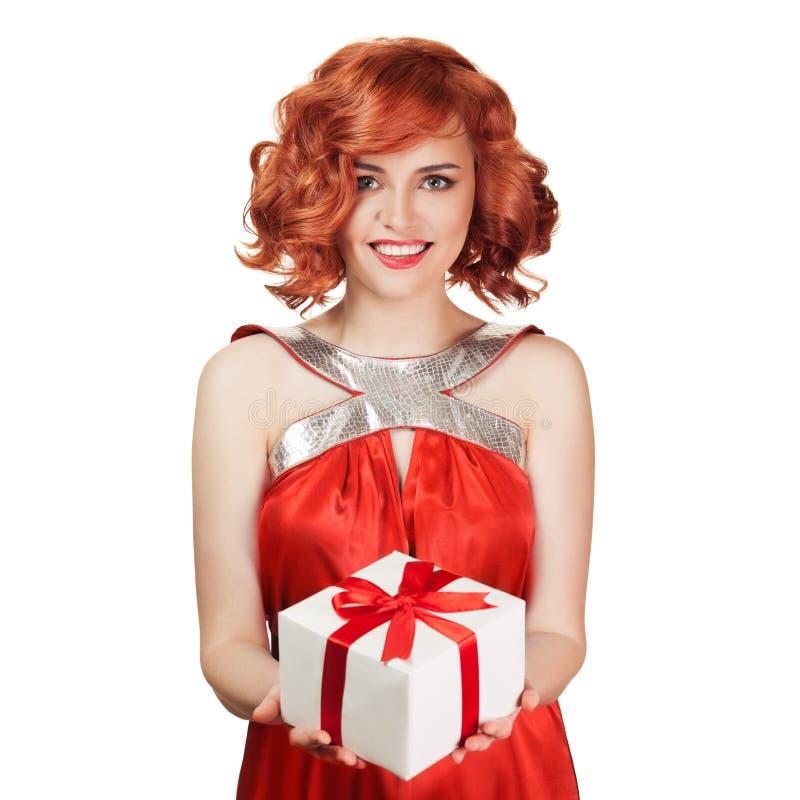 Portrait de la femme rouge de sourire de cheveux tenant le boîte-cadeau image libre de droits