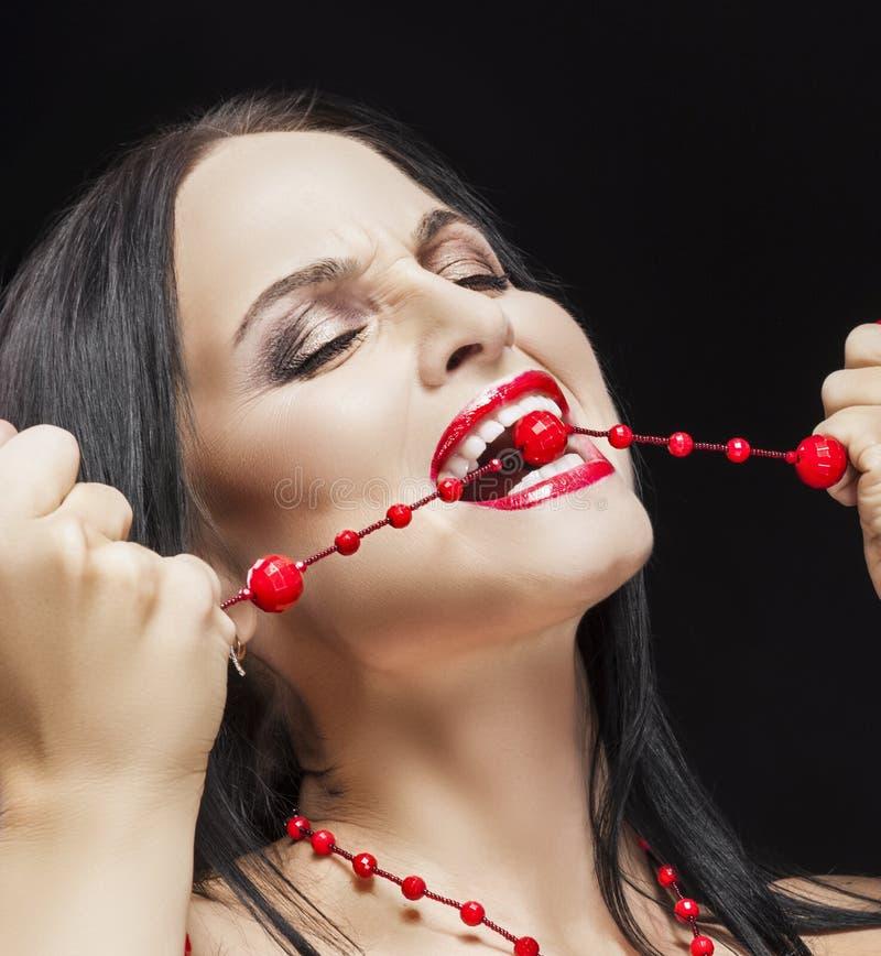 Portrait de la femme sensuelle criarde passionnée de Bunette mordant ses perles images libres de droits