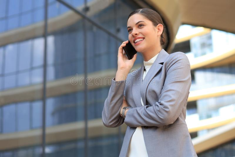 Portrait de la femme de sourire élégante d'affaires dans des vêtements à la mode invitant le téléphone portable près du bureau image libre de droits