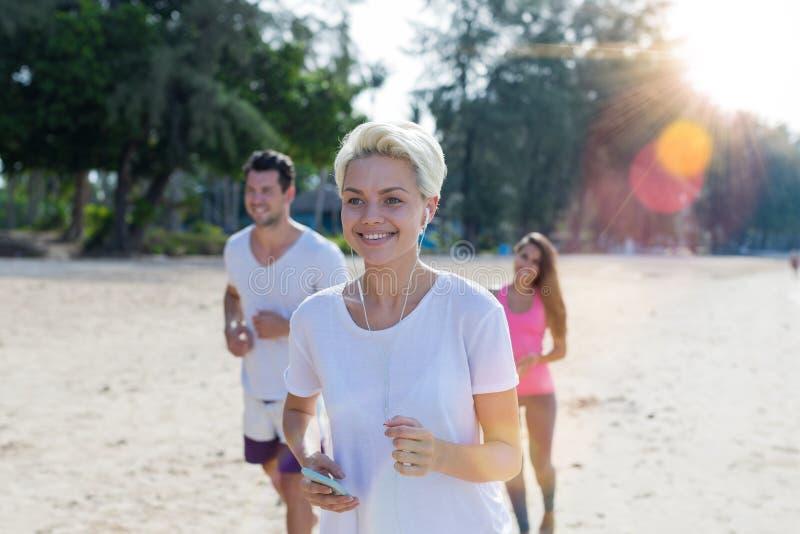 Portrait de la femme de sourire heureuse courant sur la plage avec le groupe de jeunes coureurs de sport pulsant la forme physiqu images libres de droits