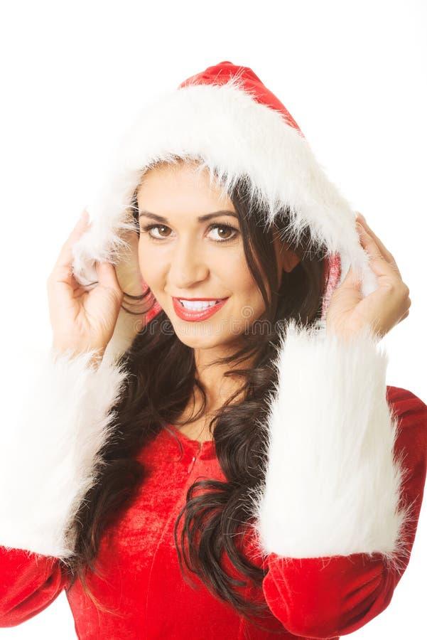 Portrait de la femme de sourire de Santa touchant son chapeau photo stock