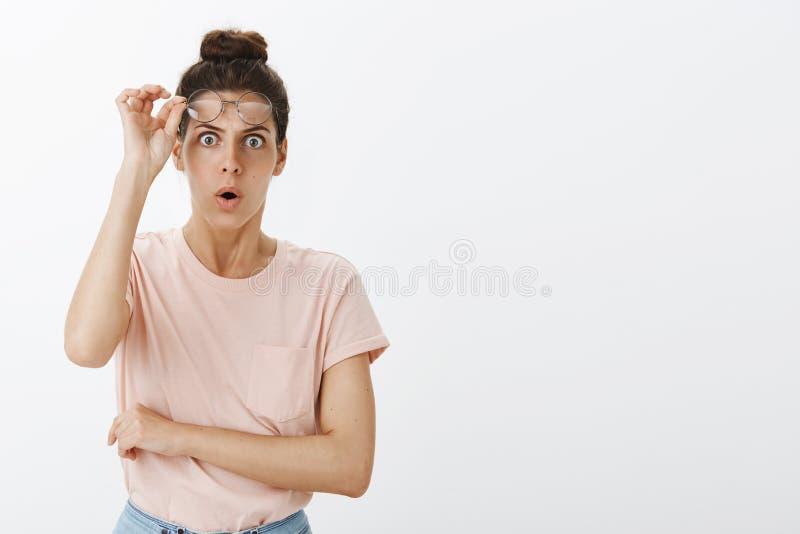 Portrait de la femme stupéfaite et choquée dans la stupeur enlevant des verres et laissant tomber la mâchoire en tant que regarde photos stock