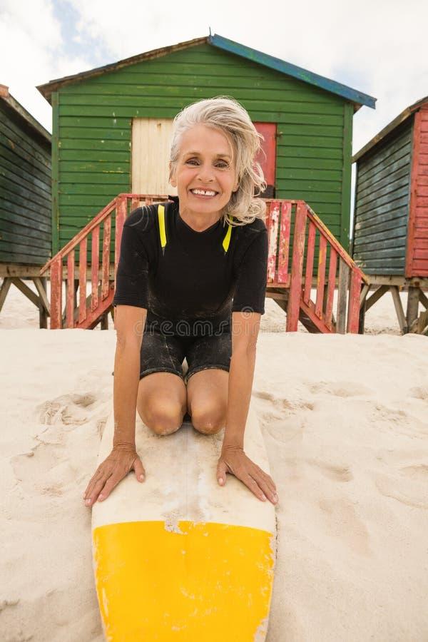 Portrait de la femme supérieure heureuse se mettant à genoux sur la planche de surf à la plage image stock