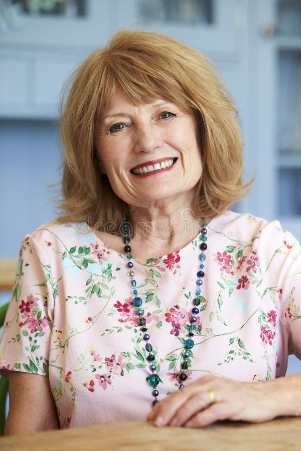 Portrait de la femme supérieure de sourire à la maison s'asseyant au Tableau photos libres de droits
