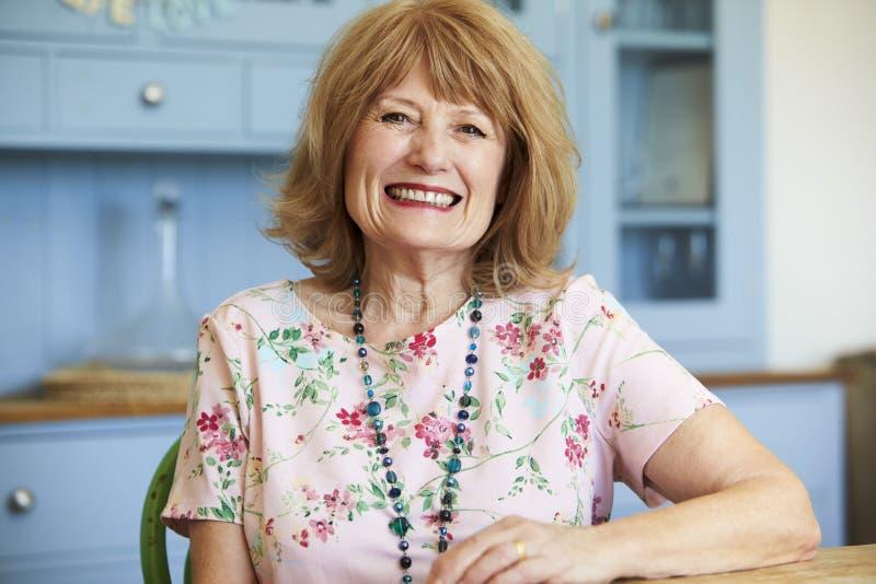 Portrait de la femme supérieure de sourire à la maison s'asseyant au Tableau photo stock