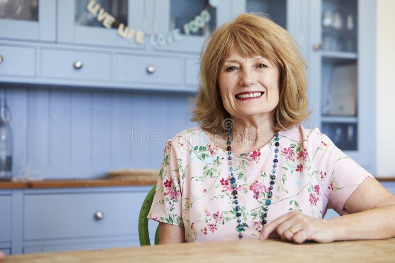 Portrait de la femme supérieure de sourire à la maison s'asseyant au Tableau images libres de droits
