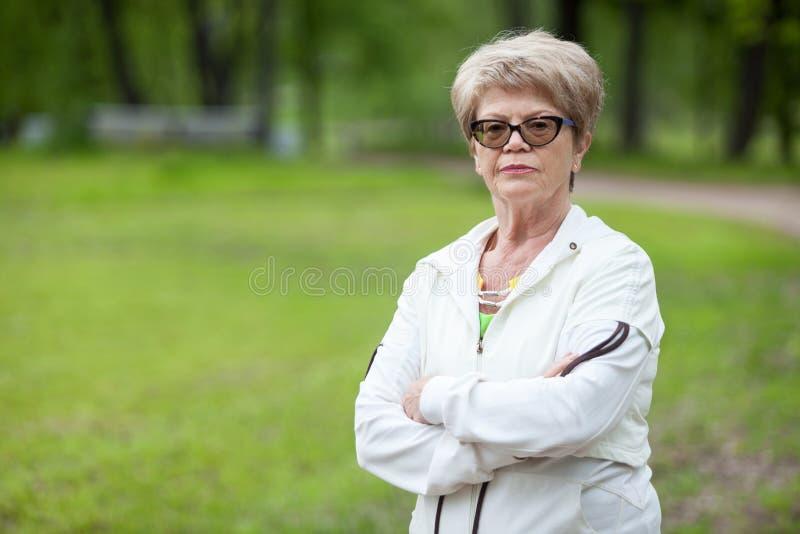 Portrait de la femme supérieure stricte sérieuse d'entraîneur se tenant avec les bras croisés, le copie-espace photo libre de droits