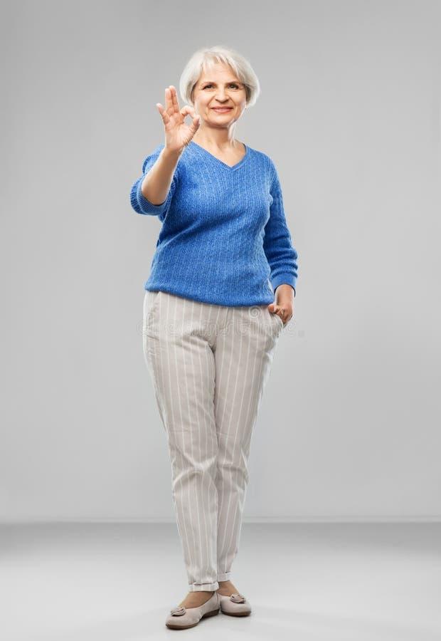Portrait de la femme sup?rieure de sourire faisant le geste correct photos libres de droits