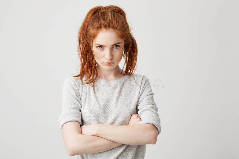 Portrait de la fille assez rousse irritée de jeunes regardant l'appareil-photo brutalement avec les bras croisés au-dessus du fon image libre de droits