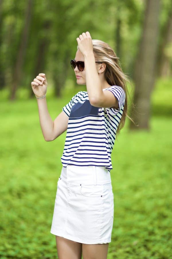 Portrait de la fille caucasienne blonde d'adolescent posant dehors dans la forêt verte images libres de droits