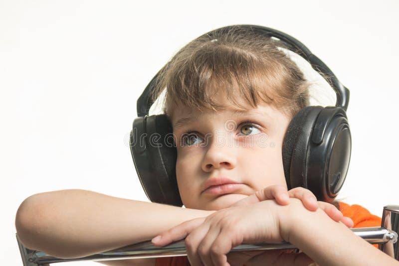 Portrait de la fille dans des écouteurs écoutant la musique musicalement image stock