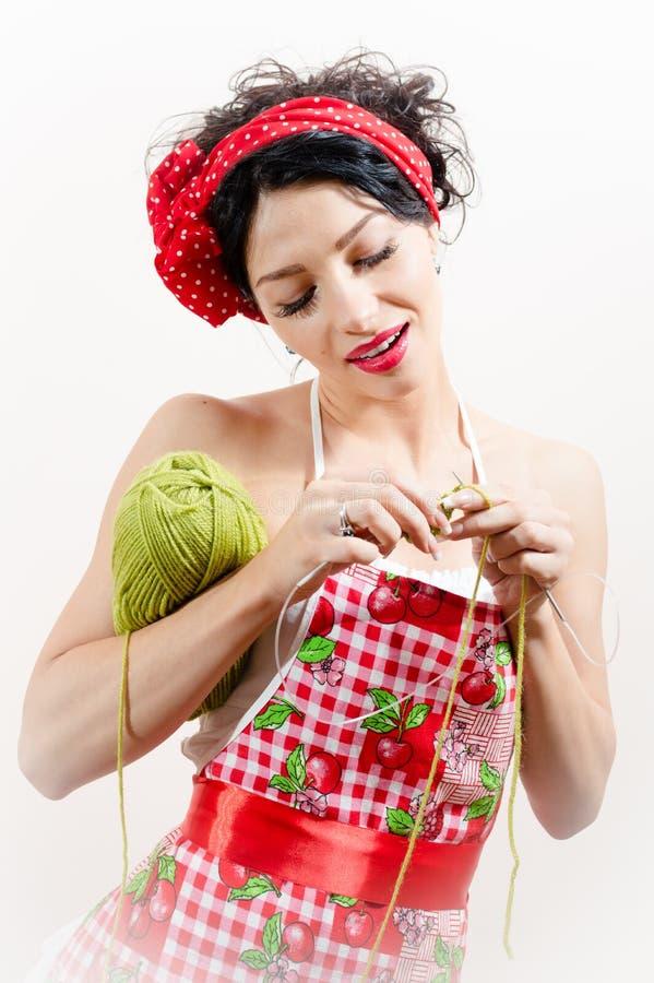 Portrait de la fille de pin-up de belle femme attirante de brune tenant le fil et les knits sur le fond blanc image stock