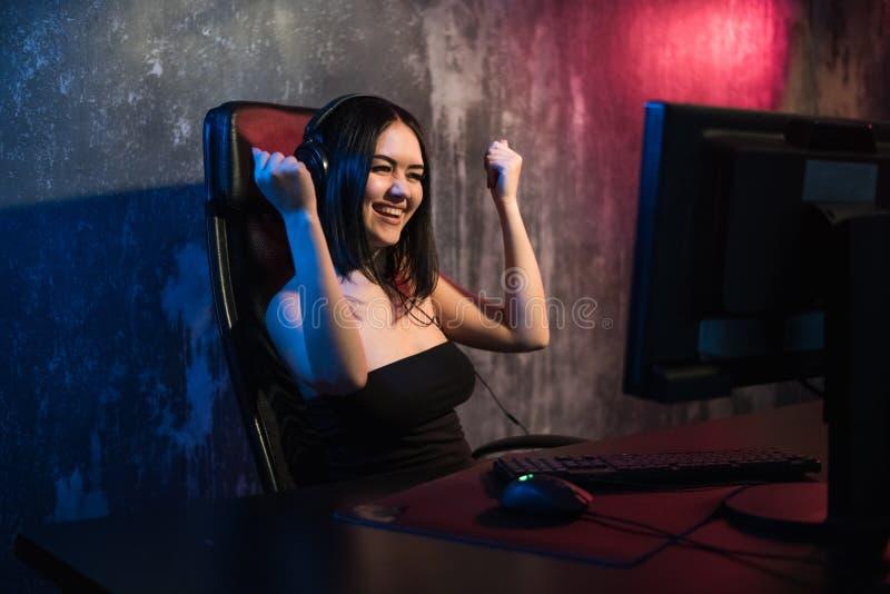 Portrait de la fille enthousiaste de gamer dans des écouteurs criant et se réjouissant tout en jouant des jeux vidéo sur l'ordina photo stock