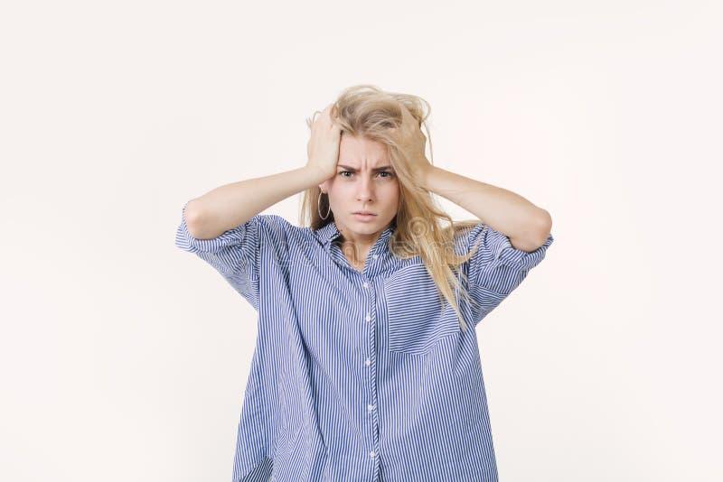 Portrait de la fille européenne blonde frustrante soumise à une contrainte habillée dans le visage de froncement de sourcils bleu photo stock