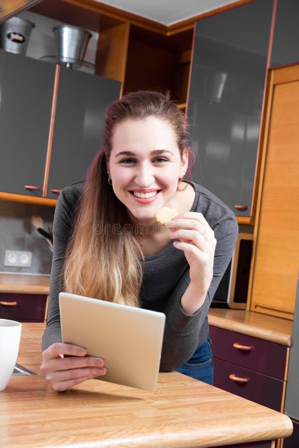 Portrait de la fille magnifique joyeuse tenant un comprimé à la maison images libres de droits
