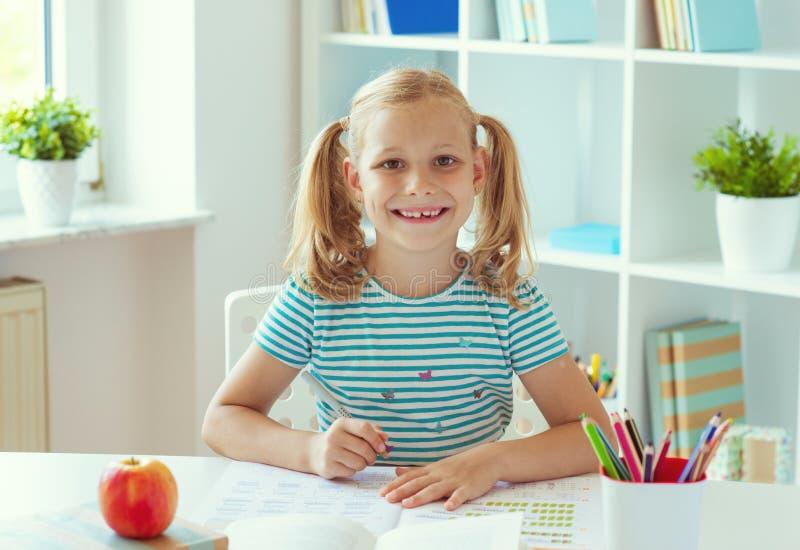 Portrait de la fille mignonne d'école s'asseyant à la table blanche à la salle de classe légère images libres de droits