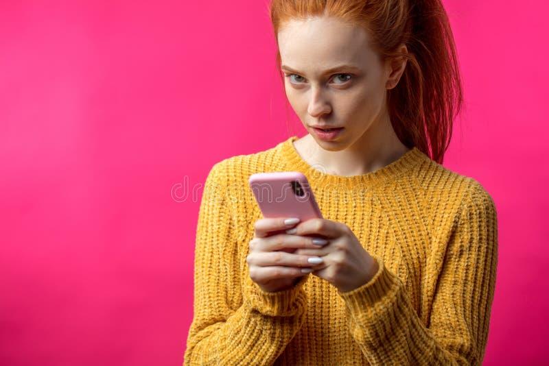 Portrait de la fille mignonne de gingembre à l'aide du smartphone d'isolement sur b rose image stock