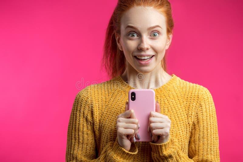 Portrait de la fille mignonne de gingembre à l'aide du smartphone d'isolement sur b rose photographie stock libre de droits