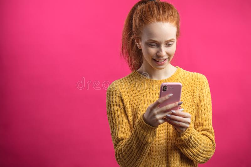 Portrait de la fille mignonne de gingembre à l'aide du smartphone d'isolement sur le fond rose image libre de droits