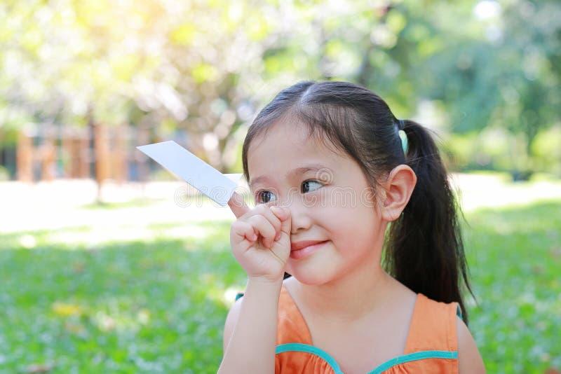 Portrait de la fille de petit enfant montrant une fusée de livre blanc sur son index au parc naturel Concept d'éducation et d'ima photos libres de droits