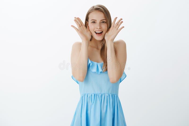 Portrait de la fille sortante charismatique et joyeuse étonnée avec les cheveux justes dans la robe habillée bleue enlevant des p photographie stock