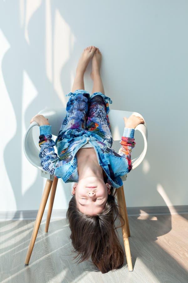 Portrait de la gentille petite fille à l'envers sur une chaise blanche photographie stock