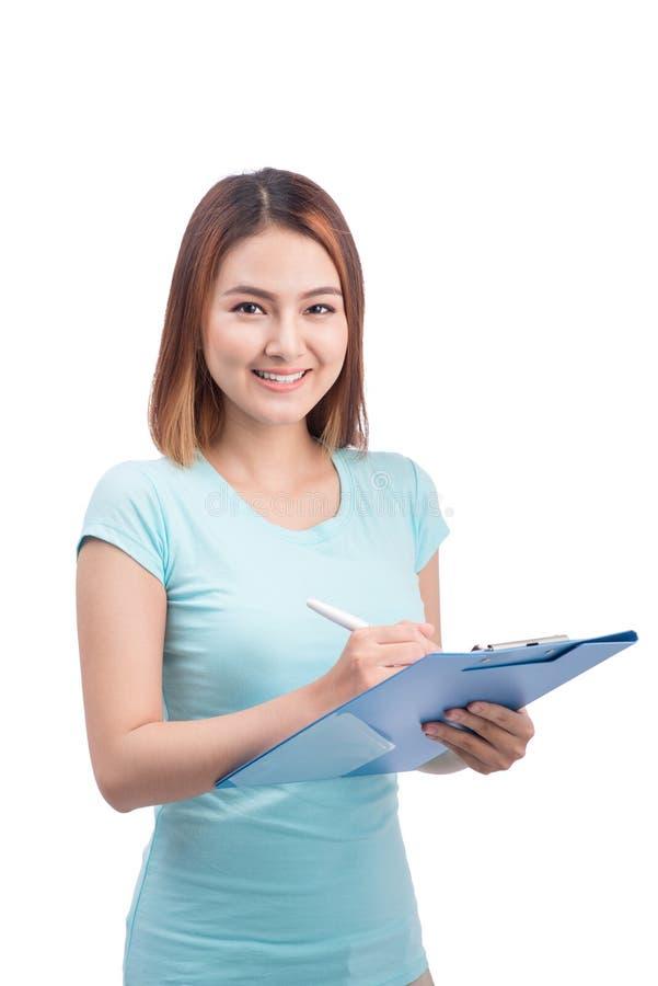 Portrait de la jeune écriture asiatique de sourire heureuse de femme sur le fol bleu photographie stock libre de droits