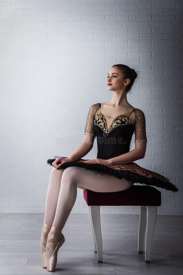 Portrait de la jeune belle ballerine parfaite s'asseyant sur la chaise à l'intérieur photographie stock libre de droits