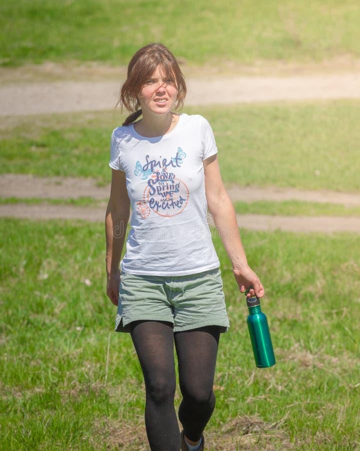 Portrait de la jeune belle brune portant l'eau potable de T-shirt bleu au parc de vert d'été photos libres de droits
