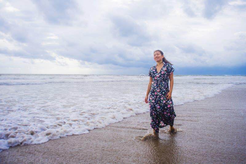 Portrait de la jeune belle et heureuse femme chinoise asiatique sur son 20s ou 30s portant la longue robe chic seul marchant sur  photographie stock