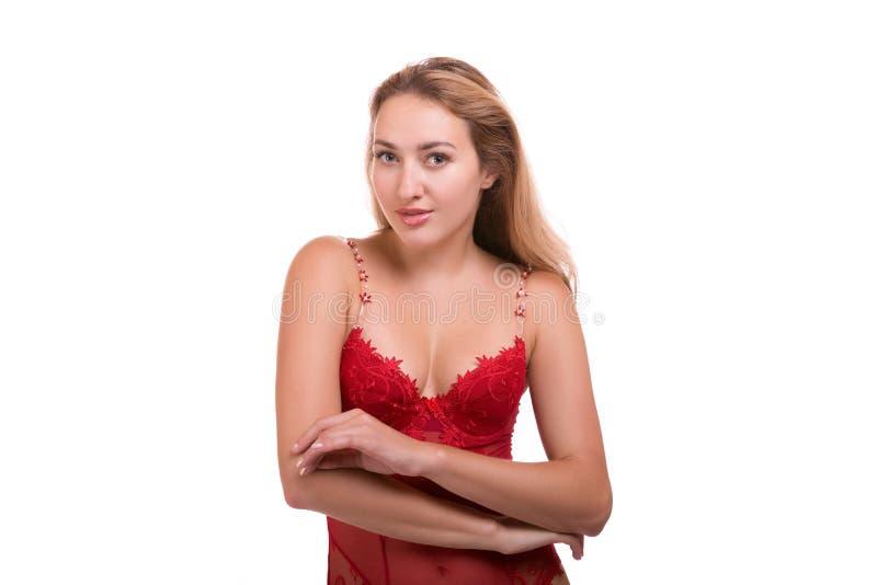 Portrait de la jeune belle femme blonde dans la pose rouge de sous-vêtements d'isolement au-dessus du fond blanc photo libre de droits